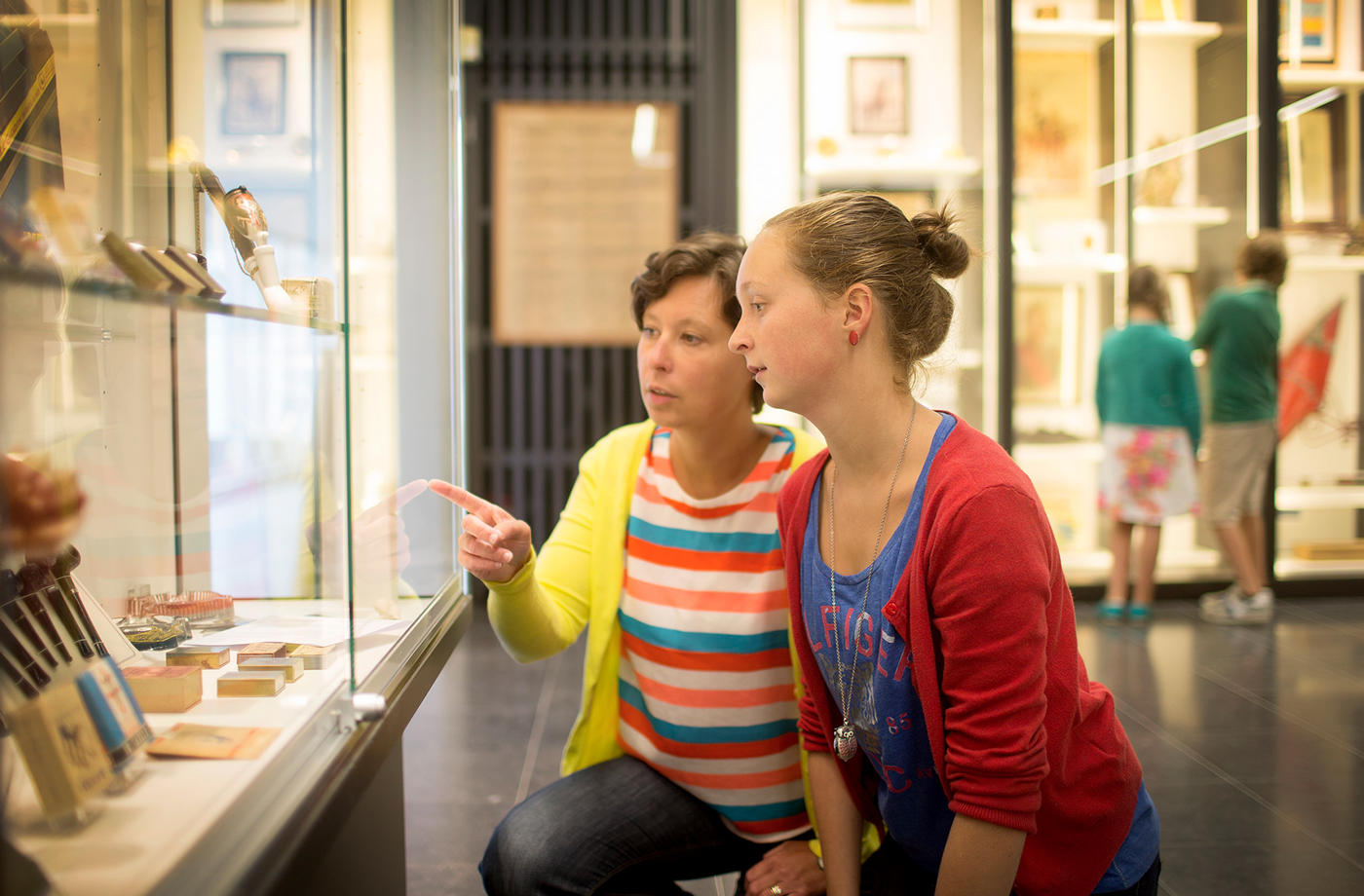 Two museum visitors observing a glass case of exhibit objects.